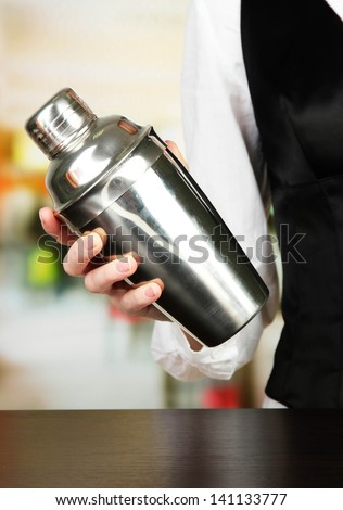 Barmen hand with shaker, on bright background - stock photo