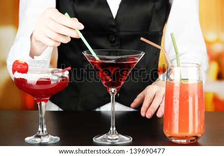 Barmen hand with shaker  pouring cocktail into glass, on bright background - stock photo