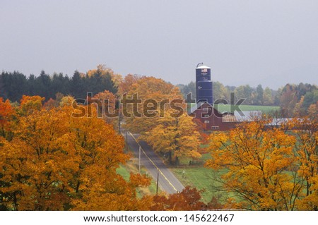 Barn and silo in autumn colors along country road, VT - stock photo