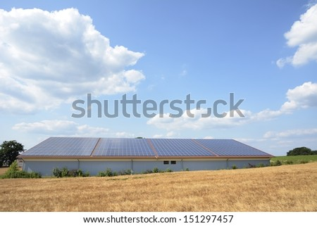 Barn at a wheat field with solar panels on the roof - stock photo