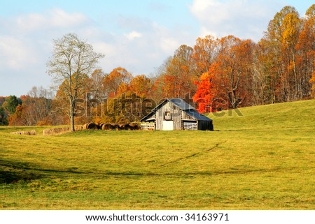 Barn with hay bales against autumn colors and a beautiful meadow with early morning light. - stock photo