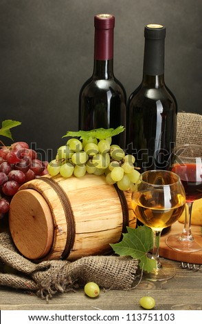 barrel, bottles and glasses of wine, cheese and ripe grapes on wooden table on grey background - stock photo