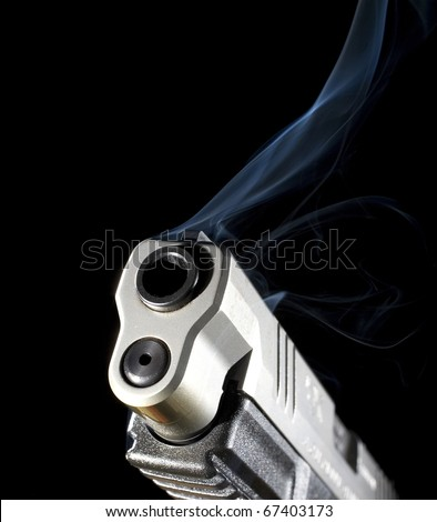 Barrel of a handgun that is so hot it is radiating blue smoke - stock photo