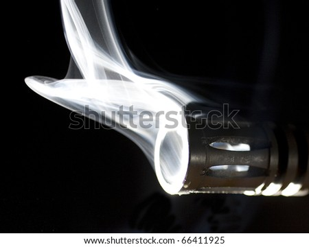 barrel on a gun that is so hot it is smoking - stock photo