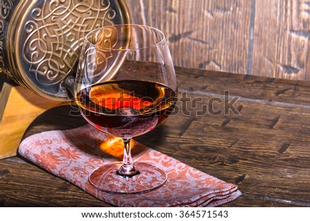 Barrel with a glass of cognac on the old table - stock photo