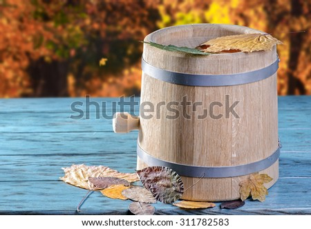 Barrel with autumn leaves - stock photo