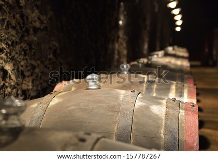Barrels of wine in an old wine cellar - stock photo