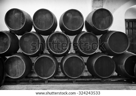 Barrels stacked in the winery in black and white - stock photo