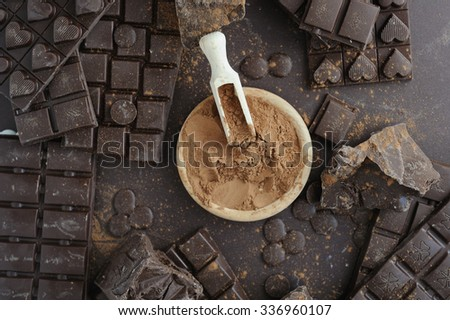 Bars, chopped and chips of  dark chocolate with cacao powder in wooden bowl - stock photo