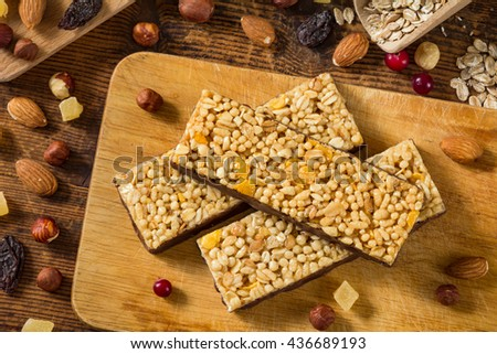 bars, granola bars on wooden cutting board surrounded with various dried fruits and nuts. Top view. Flat lay food - stock photo