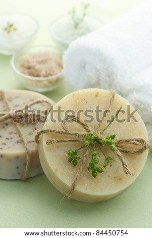 Bars of soap with bath salt and towels in light green background - stock photo