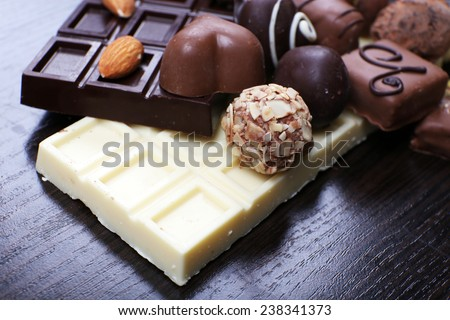 Bars of white and bitter chocolates with candies, cinnamon stick and almond on the dark wooden smooth background - stock photo