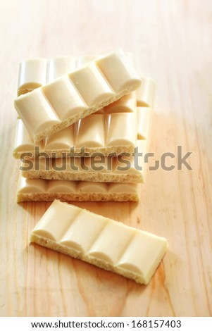Bars of white porous chocolate on wooden background - stock photo