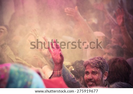 BARSANA - MAR 09: Devotees celebrate the traditional and a ritualistic Holi at Radharani temple on March 09, 2014 in Barsana, India. Holi is the most celebrated and colorful festival in India. - stock photo