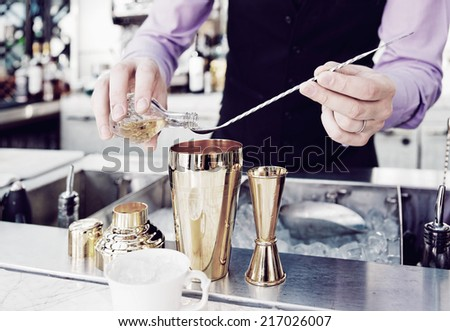 Bartender is adding ingredient in shaker at bar counter, toned image - stock photo