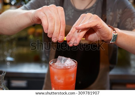 Bartender is adding zest oil to the cocktail - stock photo