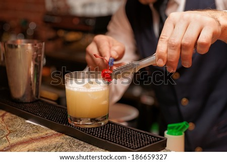 Bartender is decorating whisky sour cocktail with cherry - stock photo