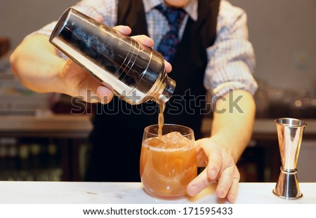 Bartender is making cocktail at bar counter  - stock photo