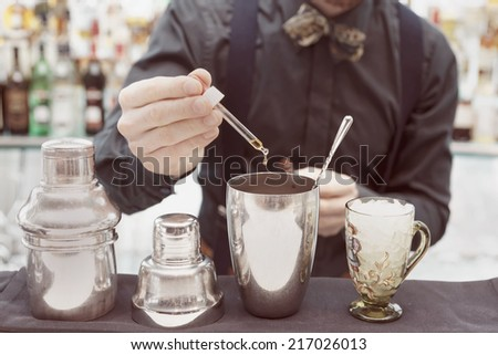 Bartender is making cocktail at bar counter, adding some bitter in the shaker, toned image - stock photo