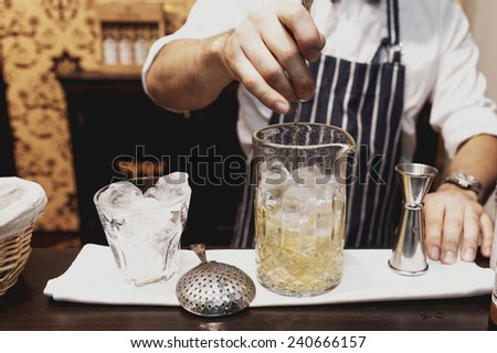 Bartender is making cocktail at bar counter, toned - stock photo