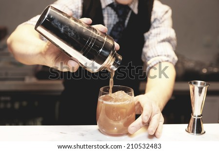 Bartender is making cocktail at bar counter , toned image - stock photo