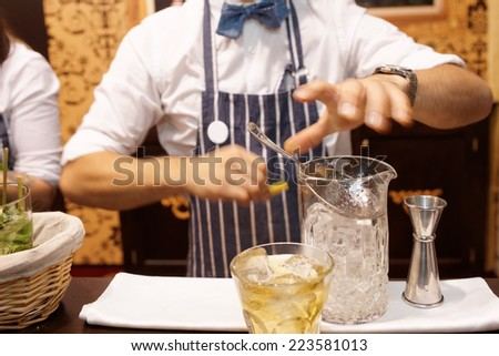 Bartender is making cocktail at bar counter, toned image - stock photo
