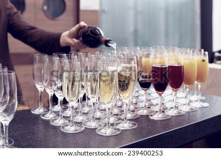 Bartender is pouring sparkling wine in glasses, making cocktails, toned - stock photo