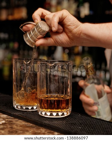 Bartender is pouring whisky in glass on the bar counter - stock photo
