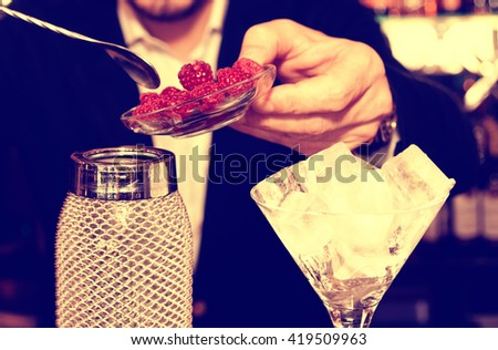 Bartender is putting fresh raspberries to a silver shaker, toned image - stock photo