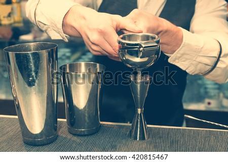 Bartender is squeezing citrus juice, toned - stock photo