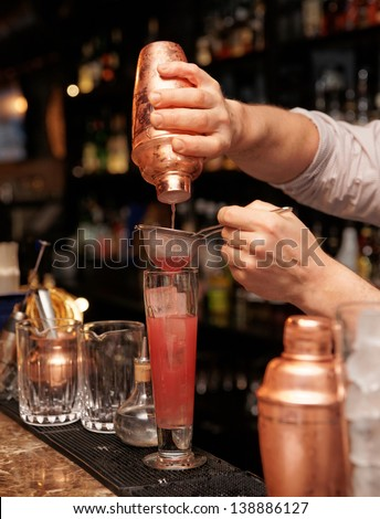 Bartender is straining cocktail in highball glass - stock photo