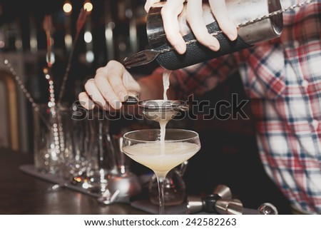Bartender is straining drink in a glass, toned, misty, bleached colors - stock photo