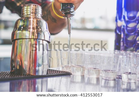 Bartender pouring alchool from the bottle in a shot glasses - stock photo