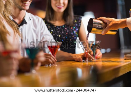 Bartender pouring cocktail for customers at the nightclub - stock photo