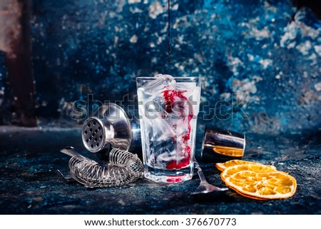 bartender pouring cranberry juice over vodka cocktail - stock photo