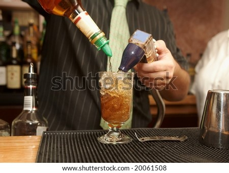 Bartender pouring mixed drink of rum and cola - stock photo