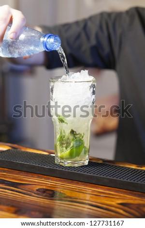 Bartender pouring soda in glass - preparing mojito - stock photo