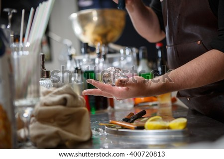Bartender pours alcoholic drink into small glasses with flames - stock photo