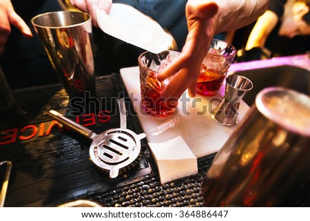 Bartender preparing a cocktail. Glass on the bar. Night life - stock photo