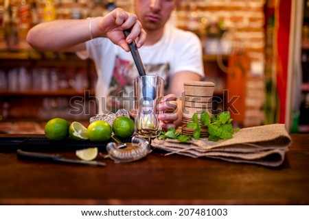 bartender preparing mojito cocktail drink, with limes, ice and brown sugar - stock photo