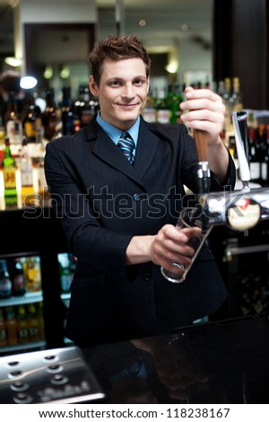 Bartender preparing to make cocktail. Assorted alcoholic beverages in the background - stock photo
