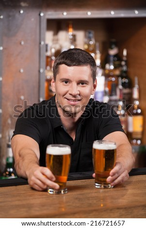 Bartender serving two glasses of beer. adult man holding beer glasses and smiling - stock photo