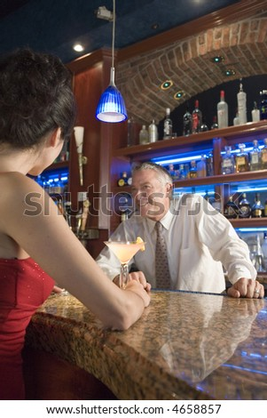 Bartender smiles at a woman while serving a drink - stock photo