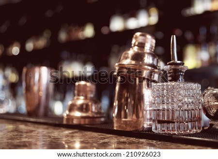Bartender tools on old style bar counter, toned image - stock photo