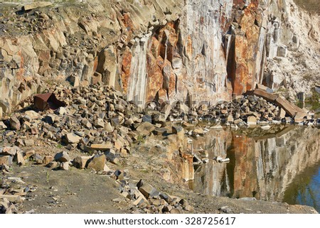 Basalt quarry on the lake - stock photo