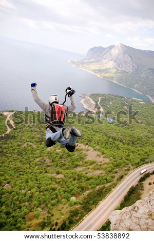 BASE jump off a cliff. - stock photo