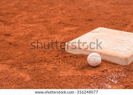 baseball and base on baseball field - stock photo