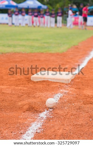 baseball and base on baseball field with players and coach on background - stock photo