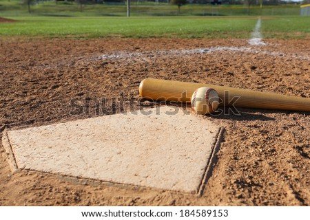 Baseball and Bat at Home Plate with the Field Beyond - stock photo