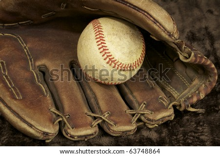 Baseball and glove, showing signs of wear. Studio shot. horizontal shot. - stock photo